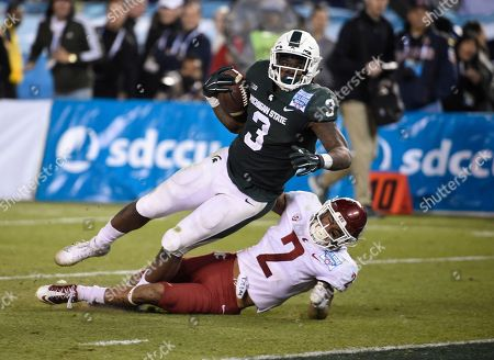 LJ Scott, Robert Taylor. Michigan State running back LJ Scott (3) scores over Washington State defensive back Robert Taylor (2) on a 28-yard run during second half of the Holiday Bowl NCAA college football game, in San Diego