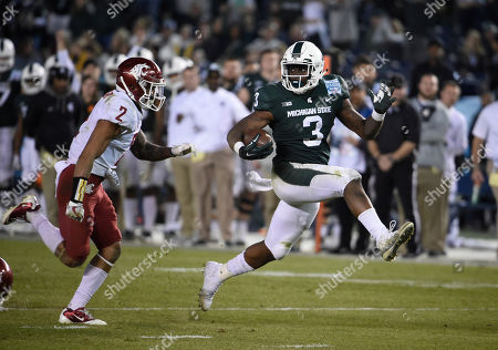 LJ Scott, Robert Taylor. Michigan State running back LJ Scott (3) looks back at Washington State defensive back Robert Taylor (2) as he scores on a 28-yard touchdown run during second half of the Holiday Bowl NCAA college football game, in San Diego