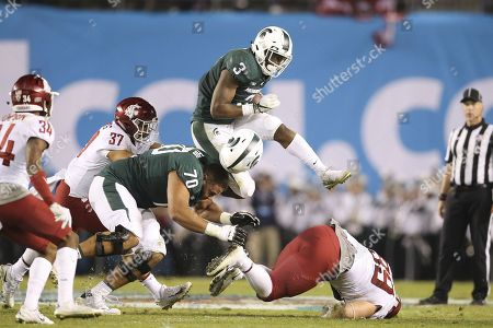 Michigan State Spartans running back LJ Scott (3) leaps Washington State Cougars defensive lineman Garrett McBroom (99) and also takes the helmet off of teammate Michigan State Spartans guard Tyler Higby (70) during a second quarter run in the game between the Washington State Cougars and the Michigan State Spartans, San Diego County Credit Union Holiday Bowl, SDCCU Stadium in San Diego, CA. Photographer: Peter Joneleit