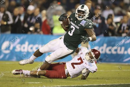Michigan State Spartans running back LJ Scott (3) breaks free for a long touchdown run and last tackle effort by Washington State Cougars defensive back Robert Taylor (2) to put the game away in the fourth quarter in the game between the Washington State Cougars and the Michigan State Spartans, San Diego County Credit Union Holiday Bowl, SDCCU Stadium in San Diego, CA. Photographer: Peter Joneleit