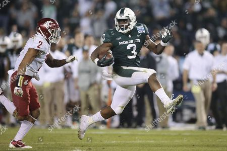 Michigan State Spartans running back LJ Scott (3) breaks free for a long touchdown run as he stutter steps by Washington State Cougars defensive back Robert Taylor (2) to put the game away in the fourth quarter in the game between the Washington State Cougars and the Michigan State Spartans, San Diego County Credit Union Holiday Bowl, SDCCU Stadium in San Diego, CA. Photographer: Peter Joneleit
