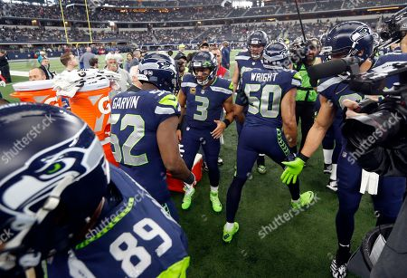 Russell Wilson, Terence Garvin, K.J. Wright. Seattle Seahawks quarterback Russell Wilson (3) greets outside linebacker Terence Garvin (52) and outside linebacker K.J. Wright (50) prior to an NFL football game against the Dallas Cowboys, in Arlington, Texas