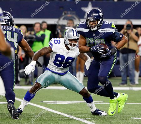 K.J. Wright, Dez Bryant. Seattle Seahawks outside linebacker K.J. Wright (50) grabs an interception in front of Dallas Cowboys wide receiver Dez Bryant (88) during an NFL football game, in Arlington, Texas