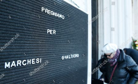 Stock Picture of A woman enterst the Milan's Santa Maria del Suffragio church during the funeral of late Italian chef Gualtiero Marchesi, Italy, . Marchesi has been the first Italian chef to be awarded with three Michelin stars