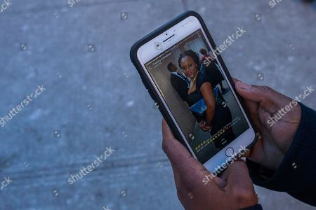 Stock Image of Sasha Answer, resident of an apartment building where there was a Thursday fire, talks to a friend as he displays a picture published in social media of Karen Stewart-Francis, who was one of more than 10 people who died in the fire, in the Bronx borough of New York, . New York City's deadliest residential fire in decades was accidentally lit by a boy playing with the burners on his mother's stove, officials said Friday
