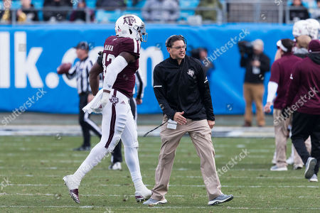 Texas A&M head coach Jeff Banks congratulates Texas A&M linebacker Otaro Alaka (42) after a stop in the matchup between Texas A&M and Wake Forest at Bank of America Stadium in Charlotte, NC