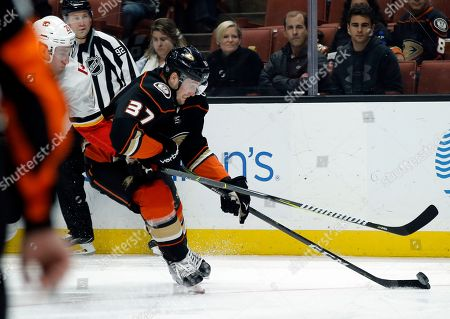 Nick Ritchie, Michael Stone. Anaheim Ducks left wing Nick Ritchie (37) controls the puck against Calgary Flames defenseman Michael Stone (26) during the second period of an NHL hockey game in Anaheim, Calif