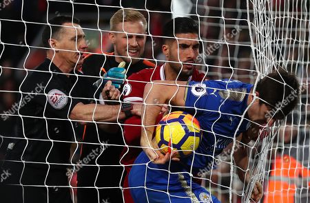 Harry Maguire of Leicester City gets tangled in the net as he clashes with Emre Can of Liverpool as goalkeeper Kasper Schmeichel and referee Neil Swarbrick try to intervene