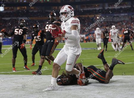 Danny David III, Sheldrick Redwine. Wisconsin wide receiver Danny Davis III (6) scores a touchdown as Miami defensive back Sheldrick Redwine (22) attempts to tackle, during the first half of the Orange Bowl NCAA college football game, in Miami Gardens, Fla