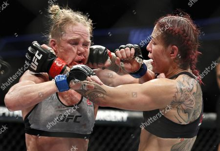 Cris Cyborg, right, hits Holly Holm during a featherweight championship mixed martial arts bout at UFC 219, in Las Vegas