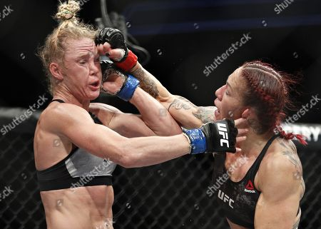 Cris Cyborg hits Holly Holm during a featherweight championship mixed martial arts bout at UFC 219, in Las Vegas