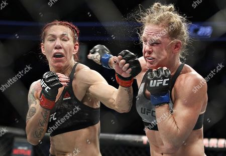Cris Cyborg, left, hits Holly Holm during a featherweight championship mixed martial arts bout at UFC 219, in Las Vegas