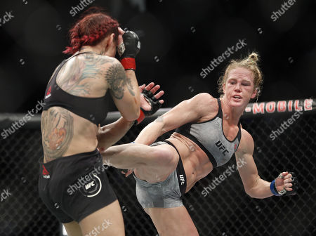 Holly Holm kicks Cris Cyborg during a featherweight championship mixed martial arts bout at UFC 219, in Las Vegas