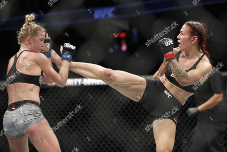 Cris Cyborg kicks Holly Holm during a featherweight championship mixed martial arts bout at UFC 219, in Las Vegas