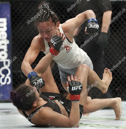 Carla Esparza, top, punches Cynthia Calvillo in a strawweight mixed martial arts bout at UFC 219, in Las Vegas