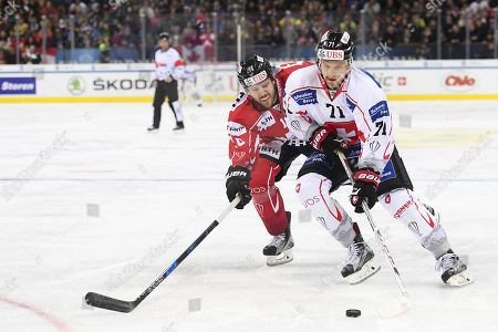 Team Canada's Curtis Hamilton, left, and Team Suisse player Richard Tanner fight for the puck during the final game between Team Canada and Team Suisse at the 91th Spengler Cup ice hockey tournament in Davos, Switzerland, Sunday, December 31, 2017.