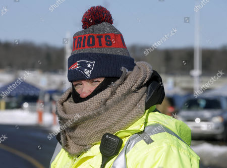 Melissa Plant, of Franklin, Mass., directs traffic in the parking lot of Gillette Stadium while bundled against the cold weather before an NFL football game between the New England Patriots and the New York Jets, in Foxborough, Mass