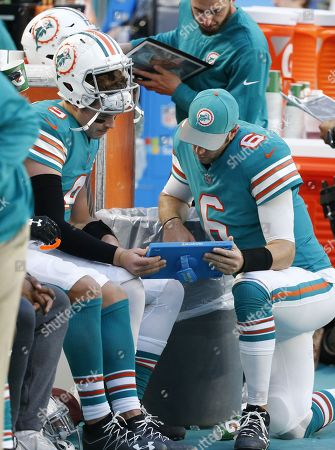 Miami Dolphins quarterbacks David Fales (9) and Jay Cutler (6) looks at plays, during the first half of an NFL football game against the Buffalo Bills, in Miami Gardens, Fla