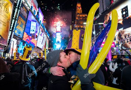 Justin Kelly, of New York, left, kisses Patrick Graver of New York, on Times Square in New York, as they take part in a New Year's celebration
