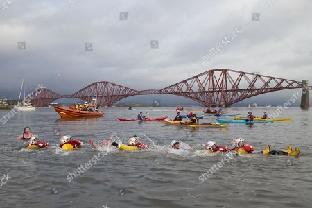 At the end of the event, Loony Dook participants Tony Pirouet, from Dunfermline, and Kenny Smith, from Rosyth, join RNLI safety swimmers in the River Forth at South Queensferry to celebrate New Year's Day and raise money for the RNLI.