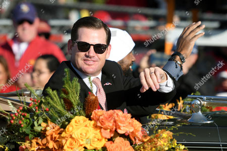Rose Bowl Hall of Fame Inductees Cade McNown, left, and Charles Woodson ride in a car at the 129th Rose Parade in Pasadena, Calif
