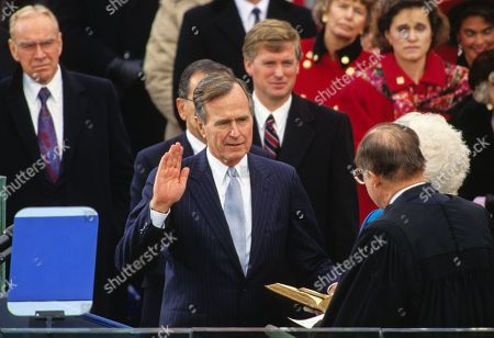 United States President George H.W. Bush is sworn-in as 41st President of the United States by Chief Justice William Rehnquist at the US Capitol. The Speaker of the US House of Representatives Jim Wright (Democrat of Texas) looks on from the left and US Vice President Dan Quayle looks on from the center.
