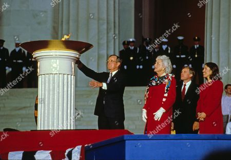 United States President-elect George H.W. Bush participates in the ceremonial candle lighting to conclude the opening ceremony for his inauguration at the Lincoln Memorial in Washington, DC. From left to right: President-elect Bush, Barbara Bush, Marilyn Quayle, and US Vice President-elect Dan Quayle.