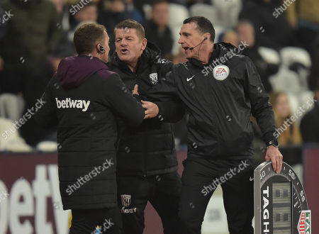 Fourth Official Neil Swarbrick has to separate assistant coaches John Carver of West Bromwich Albion and Billy McKinlay of West Ham United