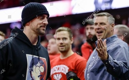 Green Bay Packers quarterback Aaron Rogers, left, is greeted by fans after watching Wisconsin defeated Indiana 71-61 during an NCAA college basketball game, in Madison, Wis