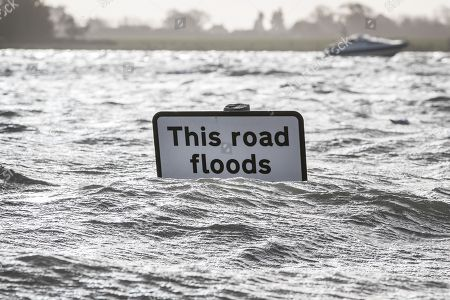 A sign on a road swamped in tidal flood water warns drivers in Bosham as storm Eleanor hits the south