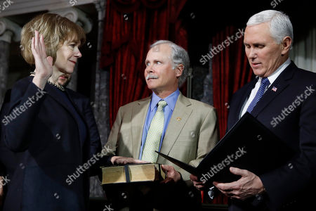 Tina Smith, Archie Smith, Mike Pence. Vice President Mike Pence, right, administers the Senate oath of office during a mock swearing in ceremony in the Old Senate Chamber to Sen. Tina Smith, D-Minn., left, with her husband Archie Smith, center, on Capitol Hill in Washington. Sen. Smith will take over from Al Franken who resigned