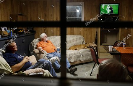 Ricky Phillips, Buddy Jones, Cary Lewis. Ricky Phillips, left, and Cary Lewis, bottom right, watch an NFL football game at the home of Buddy Jones, rear, during their weekly dinner gathering in Lumberton, N.C