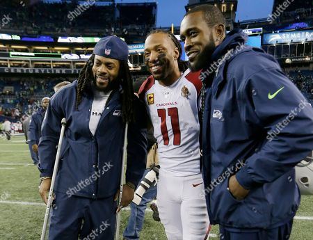 Arizona Cardinals wide receiver Larry Fitzgerald (11) poses for a photo with injured Seattle Seahawks' Richard Sherman, left, and Kam Chancellor, right, following an NFL football game, in Seattle