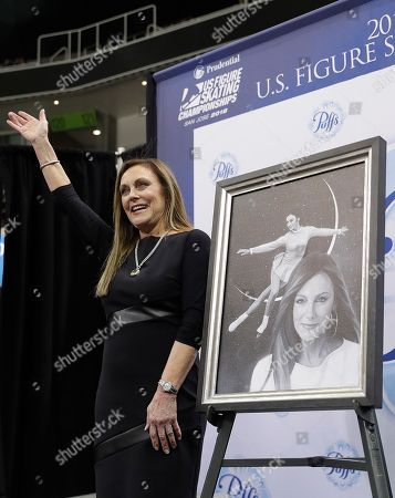 Stock Image of Peggy Fleming waves next to a painting of her at the U.S. Figure Skating Championships in San Jose, Calif