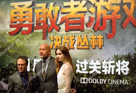 Dwayne Johnson, Karen Gillan, Jake Kasdan. From left, American director Jake Kasdan, American actor Dwayne Johnson, and British actress Karen Gillan pose for photos on the red carpet before a press conference for the movie 'Jumanji: Welcome to the Jungle' in Beijing, . The hit movie opens in China on Jan. 12