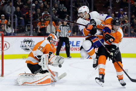 Brian Elliott, Andrew MacDonald, Cal Clutterbuck. New York Islanders' Cal Clutterbuck (15) deflects the puck past Philadelphia Flyers' Brian Elliott (37) for a goal as Andrew MacDonald (47) defends during the first period of an NHL hockey game, in Philadelphia