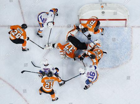 Brian Elliott, Claude Giroux, Jordan Eberle. Philadelphia Flyers' Brian Elliott (37) and Claude Giroux (28) battle for a loose puck with New York Islanders' Jordan Eberle (7) as John Tavares (91), Scott Laughton (21), Andrew Ladd (16), Andrew MacDonald (47) and Robert Hagg (8) look on during the third period of an NHL hockey game, in Philadelphia. Philadelphia won 6-4