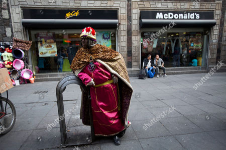 Stock Picture of Performance artist David Antonio Lopez De La Fuente Campos, dressed as one of the Three Kings, waits for families wanting to pose for souvenir photos on the eve of the Epiphany, in the historic center of Mexico City, . In Mexico, it is customary for people to give gifts on Three Kings Day also known as the Epiphany, commemorated on Jan. 6. According to Christian tradition, Jan. 6 marks the arrival of three wise men bearing gifts for the baby Jesus