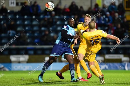 Preston North End midfielder John Welsh (19) clears his lines under pressure from Wycombe Wanderers striker Adebayo Akinfenwa (20) during the The FA Cup 3rd round match between Wycombe Wanderers and Preston North End at Adams Park, High Wycombe