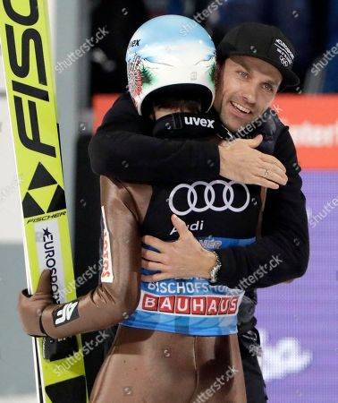 Poland's overall winner Kamil Stoch, left, is hugged by Germany's former ski jumper Sven Hannawald, right, who won all four stages of the Four Hills ski jumping event in 2002, after the Four Hills Ski Jumping event at the ski jump in Bischofshofen, Austria