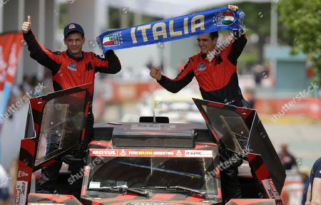 "Stock Image of Eugenio Amos, Sebastien Delaunay. Driver Eugenio Amos of Italy, right, and co-driver Sebastien Delaunay of France, hold up a banner that reads in Spanish: ""Italy"" during the Dakar Rally ceremonial start in Lima, Peru, . The 40th edition of the Dakar Rally, the tenth to be held in South America, will start in Lima on Jan. 6 to run south along the Pacific coast and cross Bolivia to finish in Cordoba, Argentina on Jan. 20"
