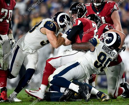 Atlanta Falcons quarterback Matt Ryan, middle, is sacked by Los Angeles Rams outside linebacker Connor Barwin, left, and nose tackle Michael Brockers during the first half of an NFL football wild-card playoff game, in Los Angeles