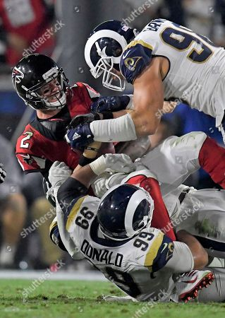 Atlanta Falcons quarterback Matt Ryan, middle, is sacked by Los Angeles Rams outside linebacker Connor Barwin, top, and defensive end Aaron Donald during the first half of an NFL football wild-card playoff game, in Los Angeles