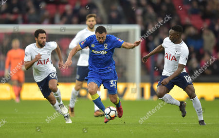 Darius Charles of AFC Wimbledon is surrounded by Mousa Dembele and Victor Wanyama of Tottenham Hotspur