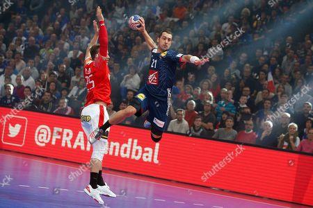 France's Michael Guigou scores a goal pasrt Denmark's Morten Olsen during their match of the Golden League handball tournament, in Paris