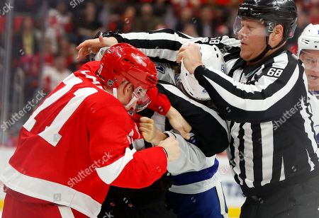 Stock Picture of Linesman Scott Driscoll (68) tries to break up a fight between Detroit Red Wings center Dylan Larkin (71) and Tampa Bay Lightning center Brayden Point (21) in the first period of an NHL hockey game, in Detroit