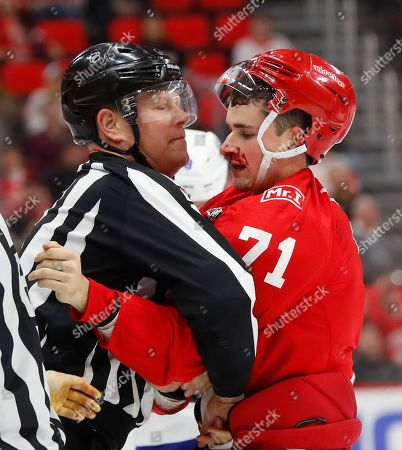 Linesman Scott Driscoll (68) holds Detroit Red Wings center Dylan Larkin (71) after a fight with Tampa Bay Lightning center Brayden Point (21) in the first period of an NHL hockey game, in Detroit