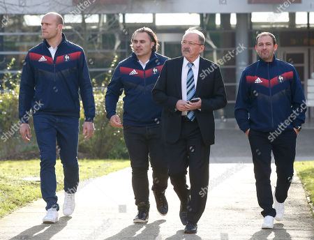 """New France Rugby coach Jacques Brunel, second right, arrives with new staff members Julien Bonnaire, left, Sebastien Bruno, second left, and Jean-Baptiste Elissalde for a media conference at the National Rugby Center in Marcoussis, south of Paris, . Brunel, who replaced Guy Noves last month, said during his first press conference on Monday that his ambition is """"to put France back to the level where it often was, so it will be among the Six Nations contenders every year"""