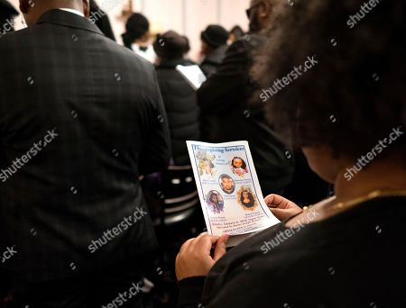 A Mourner holds a program during service for fire victims Holt Francis; his wife, Karen Stewart-Francis, 37; their daughters, Kylie, 2, and Kelesha, 7; and their cousin, Shawntay Young, 19, in New York. The family members died in a fatal fire in the Bronx borough of New York that took a total of thirteen lives on Dec. 28, 2017