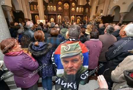 Bosnia Serbs holiday. A man wrapped in a Serb flag adorned with a photo of former Bosnian Serb military leader Ratko Mladic, pray in a church as part of ceremonies to celebrate a banned Serb holiday in the Bosnian town of Banja Luka, . The Jan. 9 holiday commemorates the date in 1992 when Bosnian Serbs declared the creation of their own state in Bosnia, igniting the country's devastating 4-year war